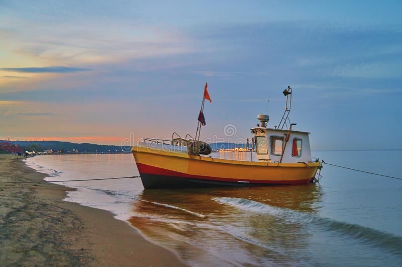 Picturesque landscape of a sunset with a fishing boat on beach in Sopot, Poland. Picturesque landscape of a sunset with a fishing boat on beach in Sopot royalty free stock photos