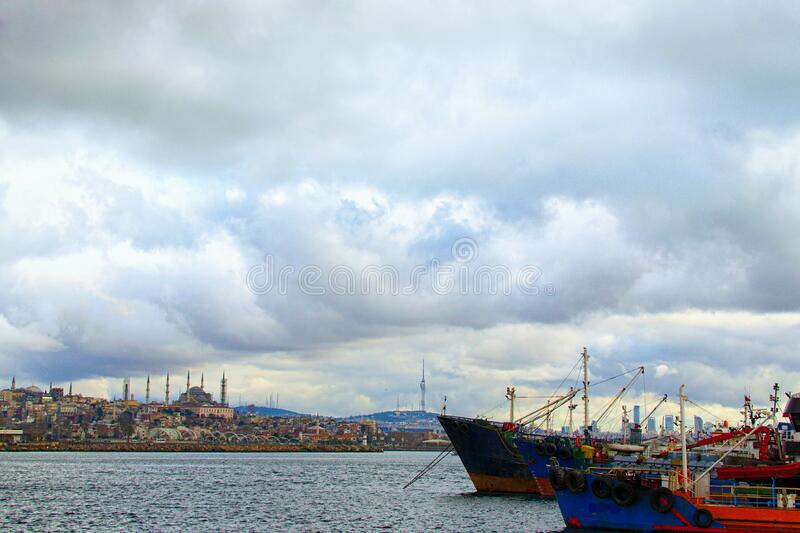 Picturesque landscape view of harbor with moored fishing boats and ships in Istanbul. Cityscape in the background. Dramatic winter sky. Istanbul, Turkey stock image