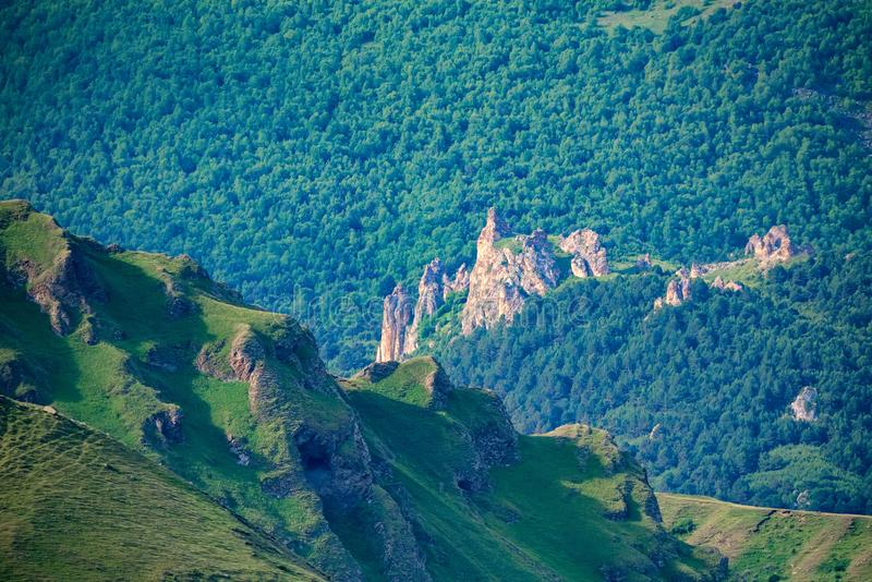 View of beautiful mountain slope in northern caucasus covered with green forest. Picturesque mountain landscape of slope covered with green lush forest in royalty free stock photos