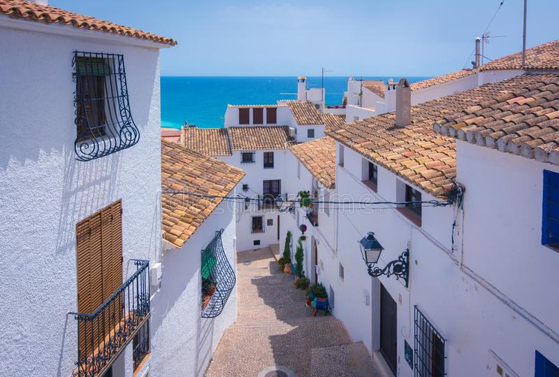 Picturesque narrow street in white village of Altea, Alicante, Spain. Picturesque narrow street with white houses in village of Altea, Alicante, Spain. Travel stock photos