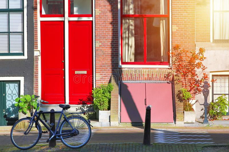 Picturesque in Netherlands. Bicycle near old house with red door and window at the canal with sunlight in Amsterdam, Nord Holland,. Netherlands stock image