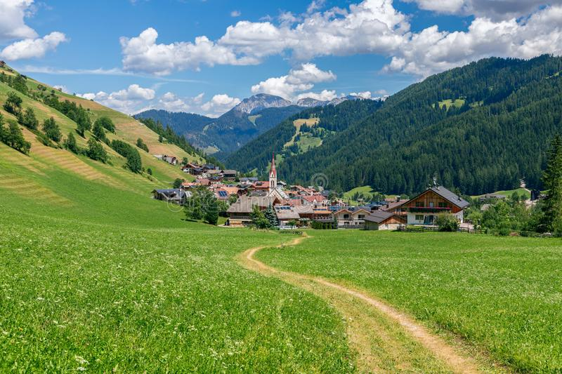 Picturesque path leading to a small beautiful alpine town Longiaru Campill stock photos