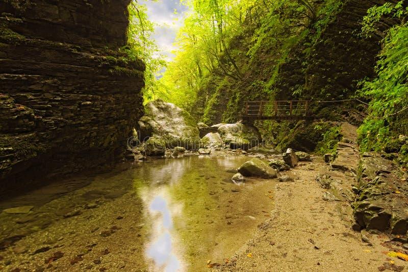 Picturesque pathway to the famous Kozjak Waterfall Slap Kozjak. Narrow path with small bridge over river. stock photo