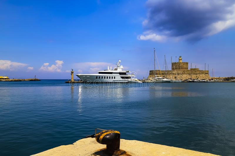 Picturesque port on the sea - dock, white ship, medieval fortress, turquoise and blue water. Rhodes, Greece. Europe royalty free stock photos