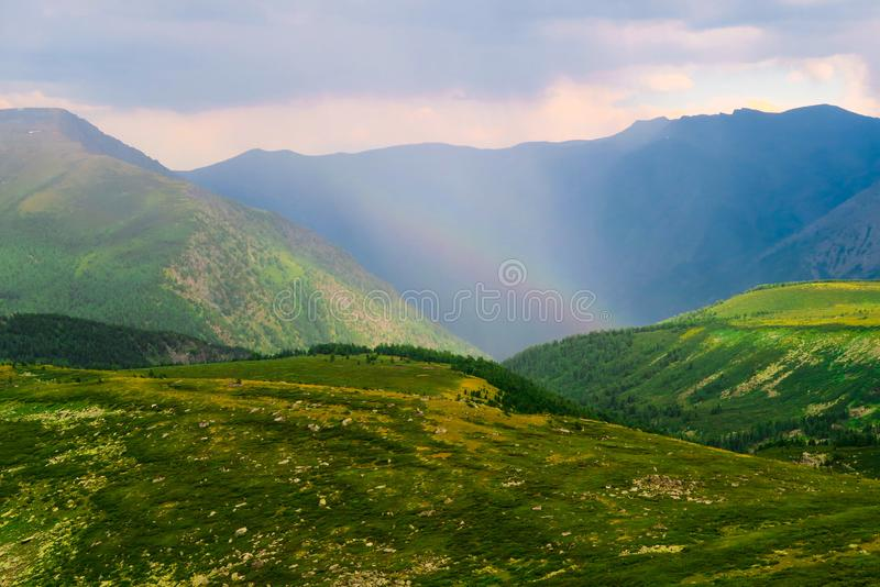 Picturesque rainbow in the mountains. Amazing mountains valley scenic view after the rain. Altai mountains royalty free stock photography