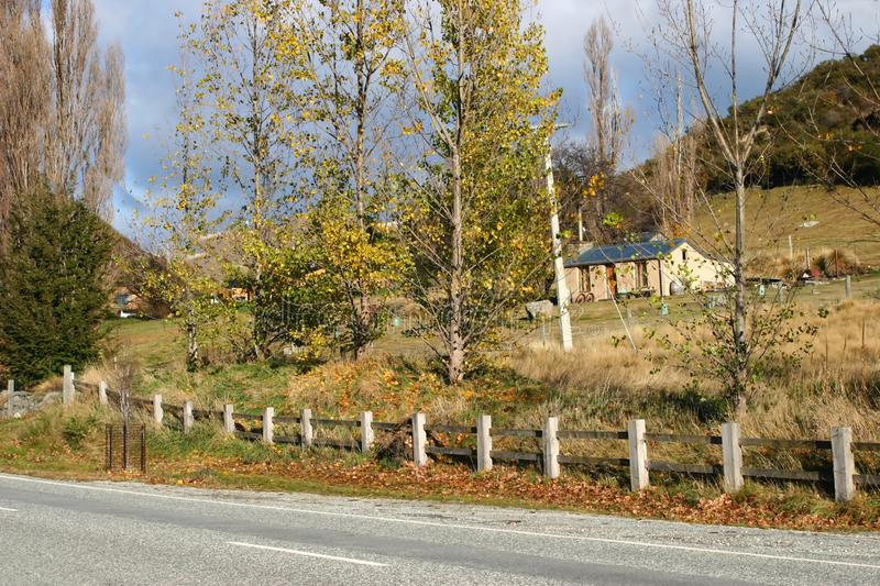 Picturesque roadside country home with wood fence and trees on high ground in autumn. House on countryside highway on South Island, New Zealand stock image