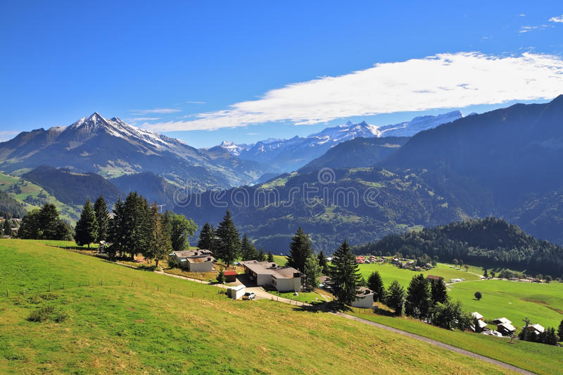 Picturesque rural houses chalets with red roofs. Picturesque gentle alpine meadows and rural houses chalets with red roofs. Gorgeous weather in the resort town royalty free stock photos