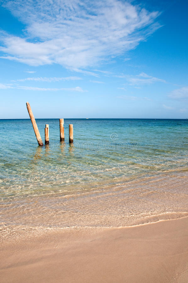 Picturesque sandy beach. Scenic view of picturesque sandy beach with wooden posts in sea and blue sky and cloudscape background royalty free stock photography