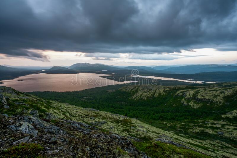 Picturesque scenery of wild landscape scenery with dramatic rain clouds during sunset hours. Hiking and travel concept royalty free stock images