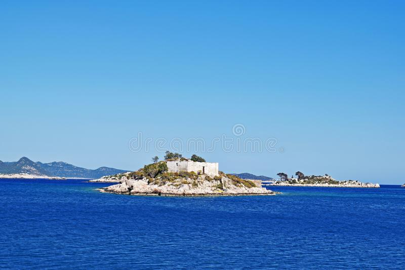 A sea view on a summer`s day. Picturesque sea view of the crystal clear blue water of the Mediterranean sea surrounding the small islands and the mountains in stock images
