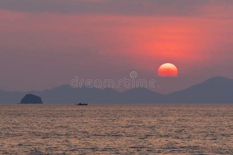 Large red circle of sun in a haze sets behind the silhouette of the mountains and clouds on the stock photography