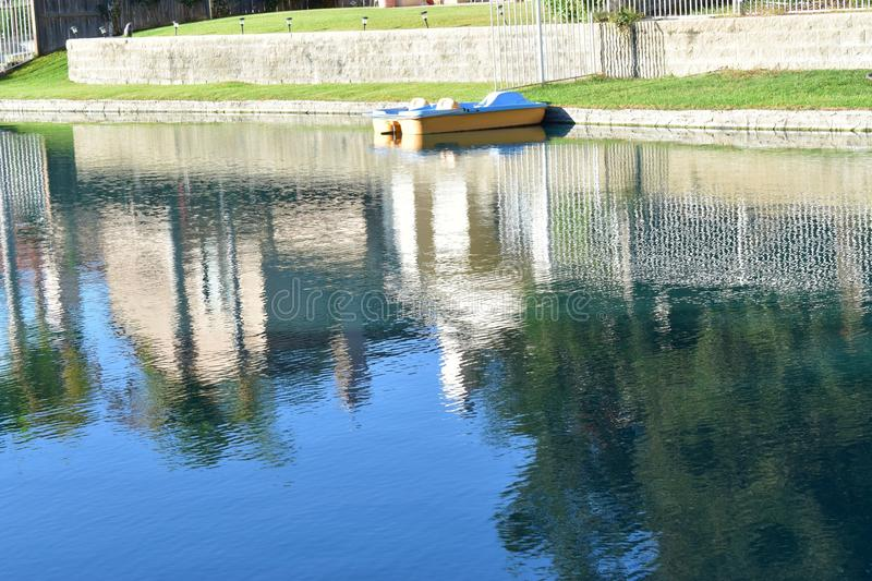 Reflection of boats and outside architecture on the serene lake royalty free stock photography