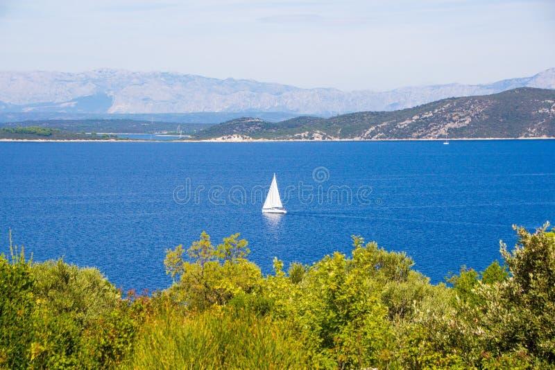 Picturesque stagcapé Una piccola barca bianca sullo sfondo di mare blu e montagne fotografia stock libera da diritti