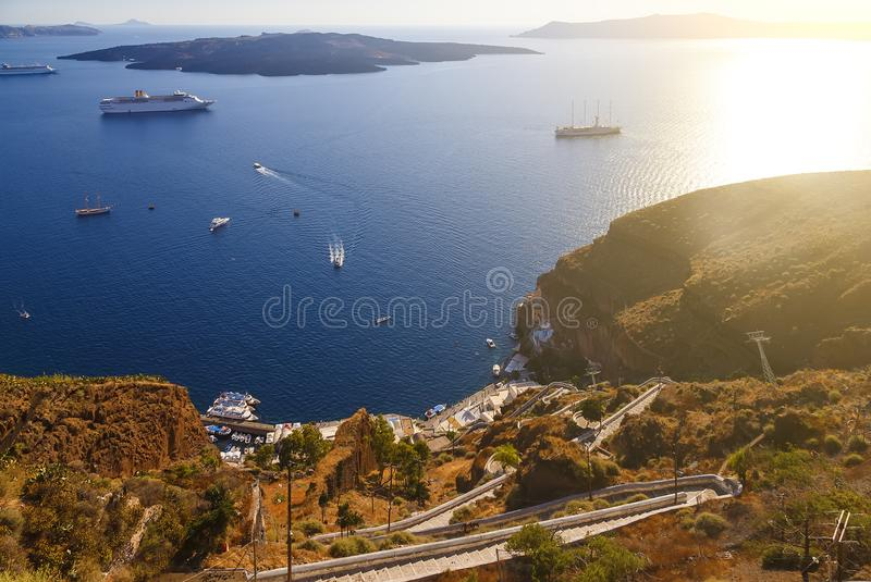 Picturesque staircase down to sea, Oia, Santorini. Top view on the sea with ship and boats at the pier, Greece. stock photos