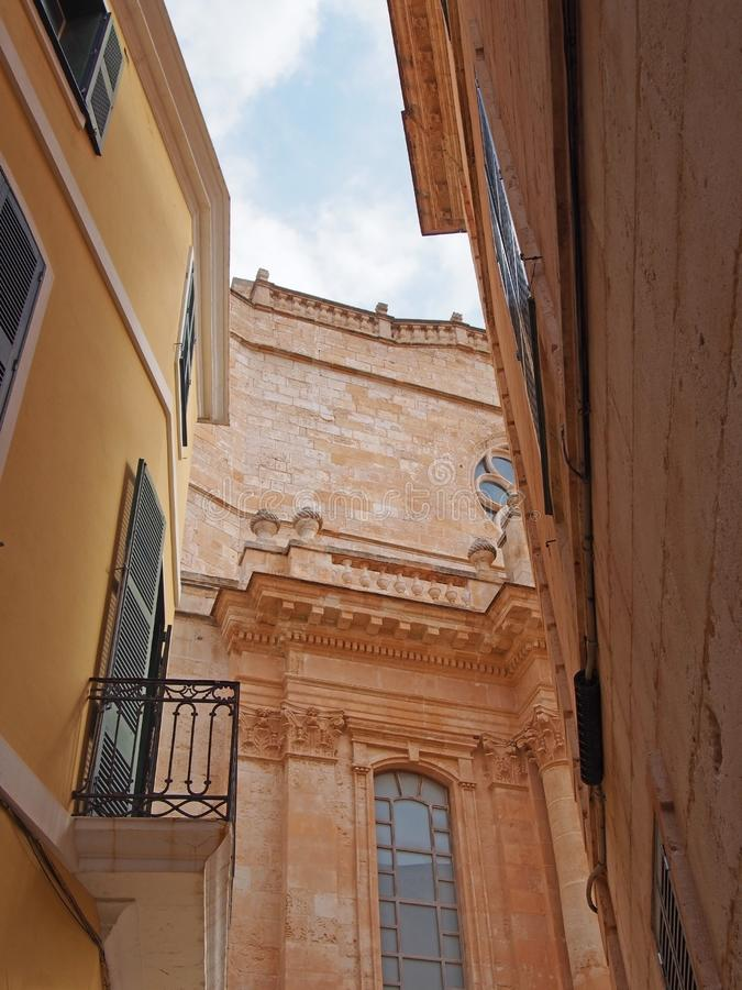 Picturesque street view of ciutadella looking upwards at the facade of the cathedral with old shuttered windows and balconies. A picturesque street view of stock photos
