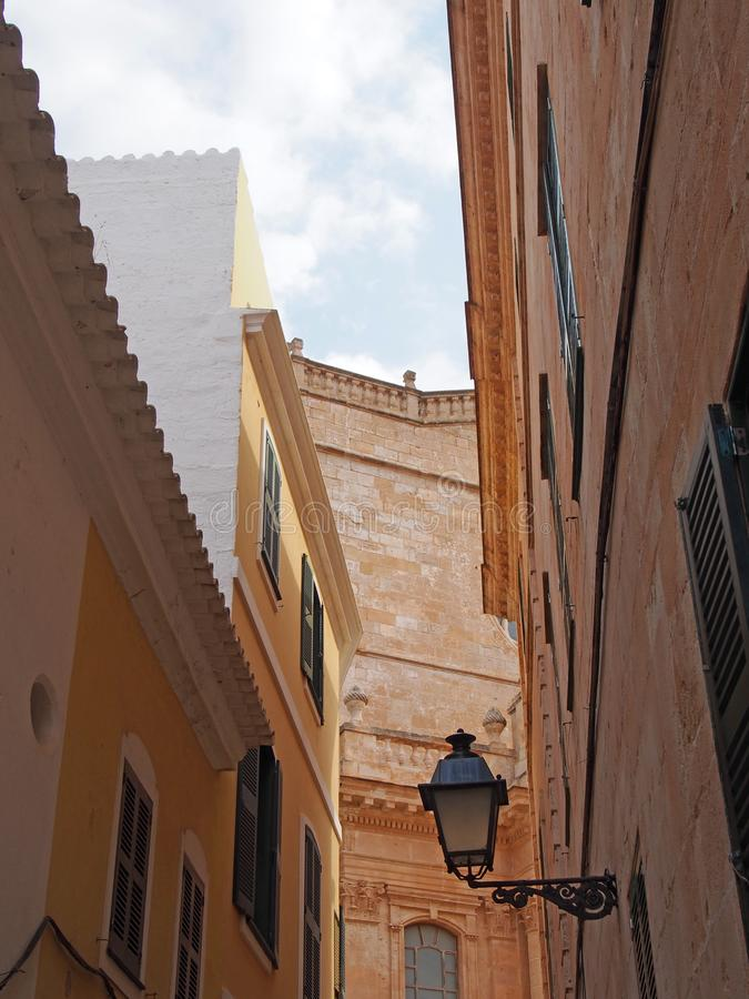 Picturesque street view of ciutadella looking upwards at the facade of the cathedral with old shuttered windows and balconies. Against a blue summer sky royalty free stock photography