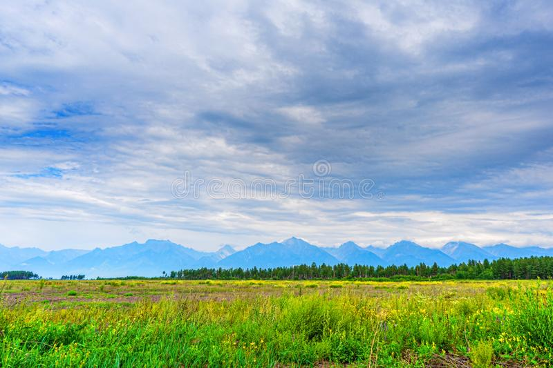 Picturesque summer landscape of mountain range with peaks, valley with green grass, grove and cloudy sky. Natural background with stock photo