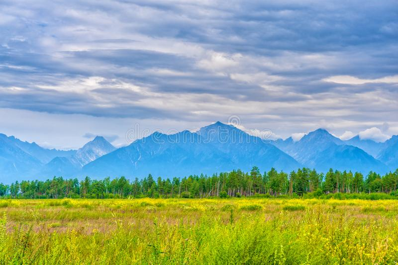 Picturesque summer landscape of mountain range with peaks, valley with green grass, grove and cloudy sky. Natural background with stock image
