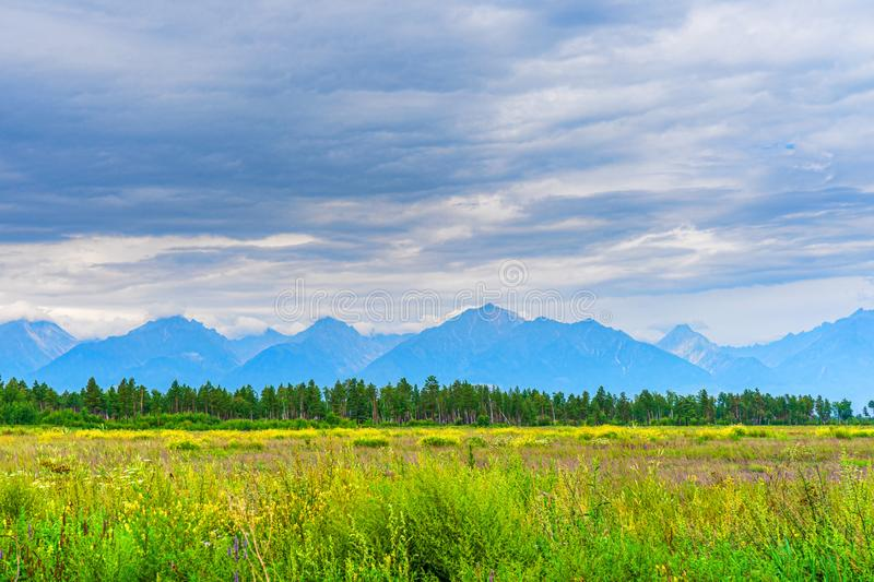 Picturesque summer landscape of mountain range with peaks, valley with green grass, grove and cloudy sky. Natural background with royalty free stock images