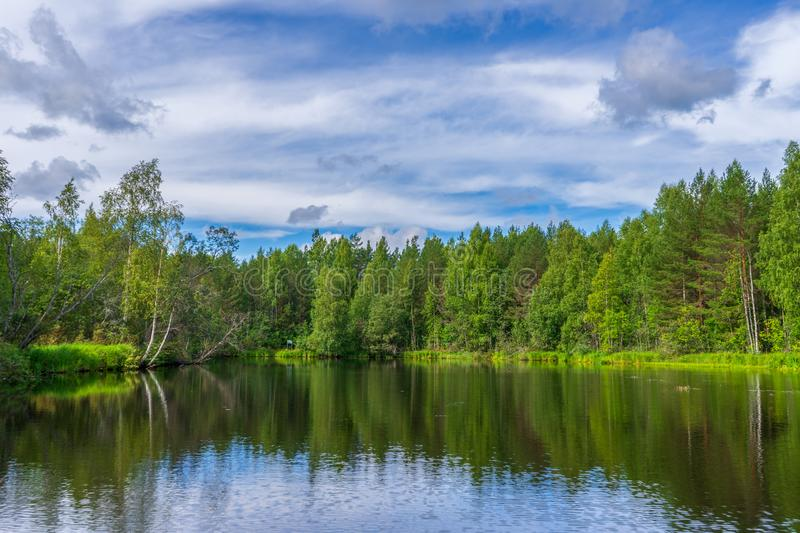 Picturesque summer landscape with northern river and forest in summer cloudy day. Travelling and discovering distant places of stock images