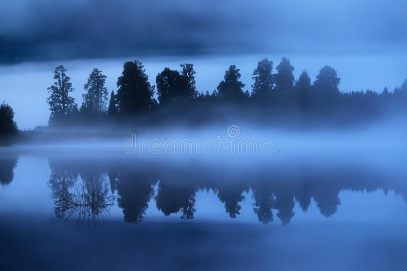 Picturesque sunrise scenery on the lake with misty trees reflected in the water. Beautiful natural background stock images