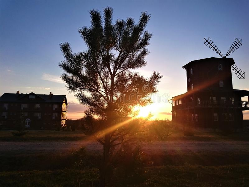 A picturesque sunset against a blue sky, houses and a mill stock photos