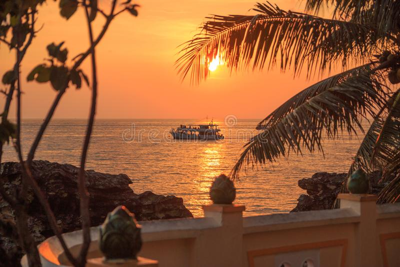 Picturesque sunset near the sea with coconut palm tree, orange sun, boat and clouds. Phu Quoc, Vietnam. royalty free stock photos