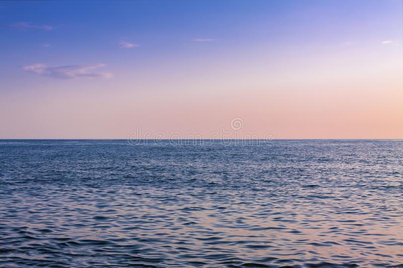 Picturesque sunset over the blue surface of the sea. Water, sky, nature, ocean, landscape, sunrise, horizon, summer, orange, beautiful, beach, sunlight stock image