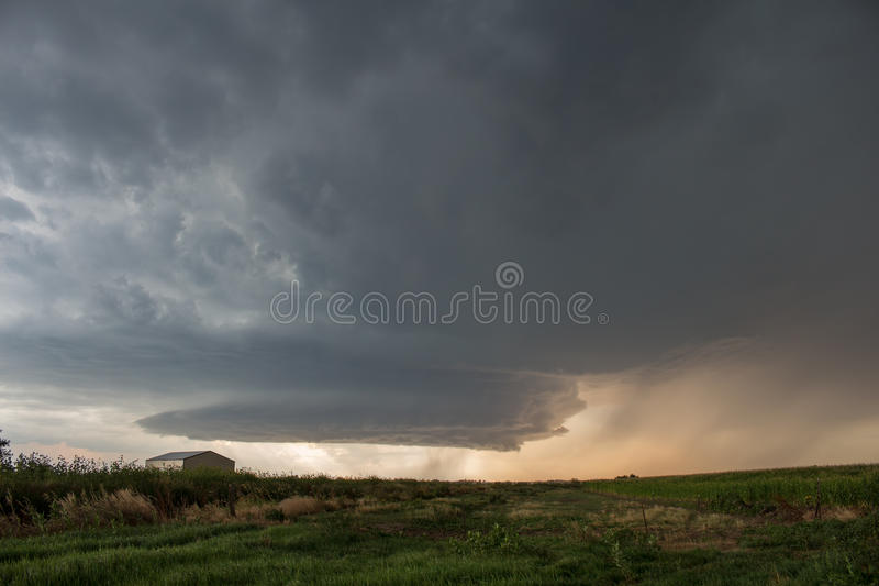 A picturesque supercell thunderstorm spins over the high plains of eastern Colorado. Dropping hail and curtains of rain as it approaches stock photo