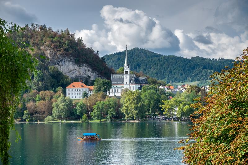 Picturesque view on church and wooden flat-bottom boat Pletna at Lake Bled stock photography