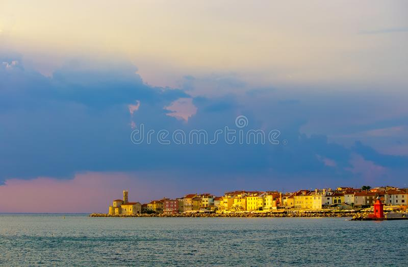 Picturesque view of coastline of Adriatic sea with colorful houses and lighthouse at sunset, Piran, Slovenia stock image