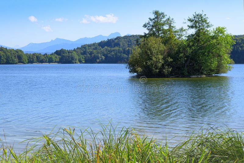 Picturesque view of small lake with wooded islet royalty free stock images