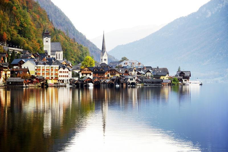 The picturesque village of Hallstatt is reflected in the lake in a sunny autumn day stock photography