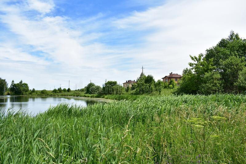 Picturesque village pond high grass clouds in the sky stock images