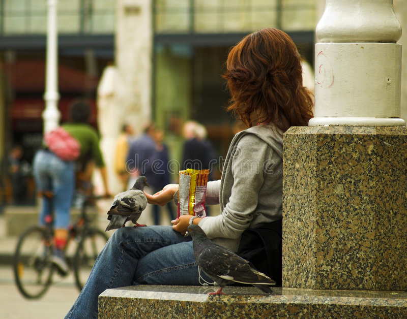 Pidgeon mangeant de la main de la fille photo stock