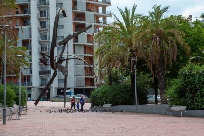 Pidgeons de jeu et de alimentations de famille à côté de sculpture à Barcelone images stock