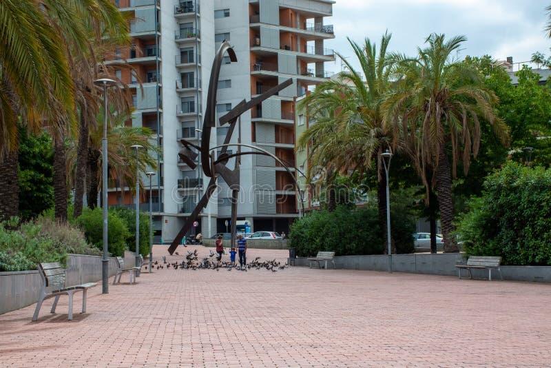 Pidgeons de jeu et de alimentations de famille à côté de sculpture à Barcelone photo libre de droits