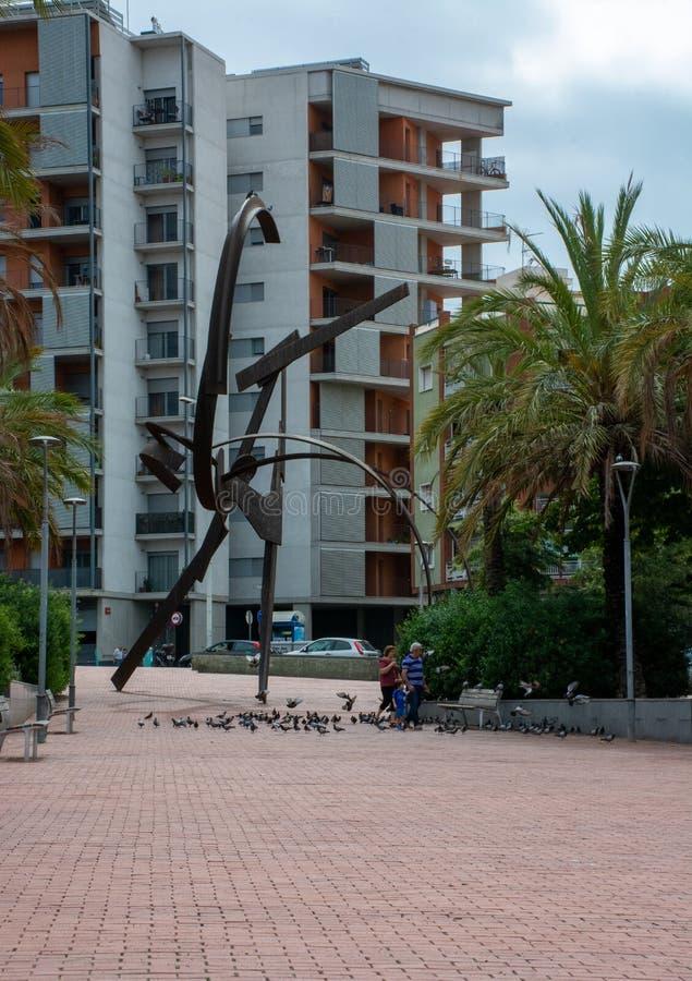 Pidgeons de jeu et de alimentations de famille à côté de sculpture à Barcelone image stock