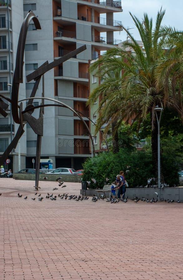 Pidgeons de jeu et de alimentations de famille à côté de sculpture à Barcelone photographie stock