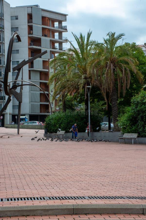 Pidgeons de jeu et de alimentations de famille à côté de sculpture à Barcelone photos libres de droits