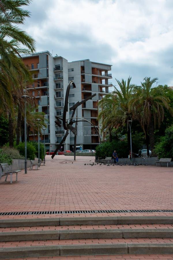 Pidgeons de jeu et de alimentations de famille à côté de sculpture à Barcelone photo stock