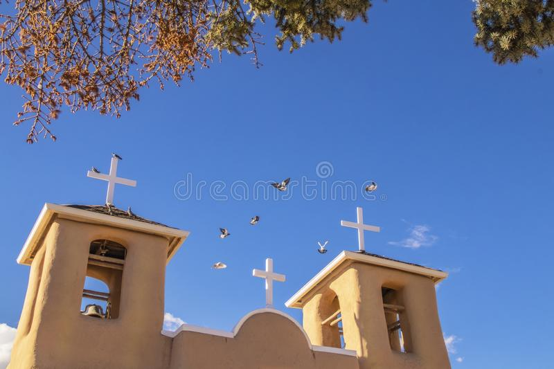 Pidgeons flying above the roof and bell towers of the famous adobe San Francisco de Asis Mission Church on the main plaza of Ranch stock image