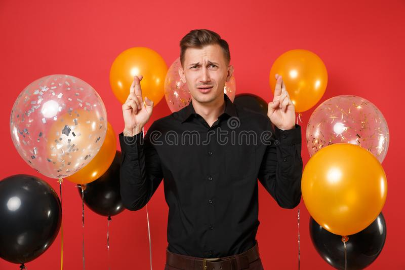 Pidiendo al hombre joven en la camisa clásica negra que mantiene los fingeres cruzados haciendo deseo en los balones de aire rojo imagenes de archivo