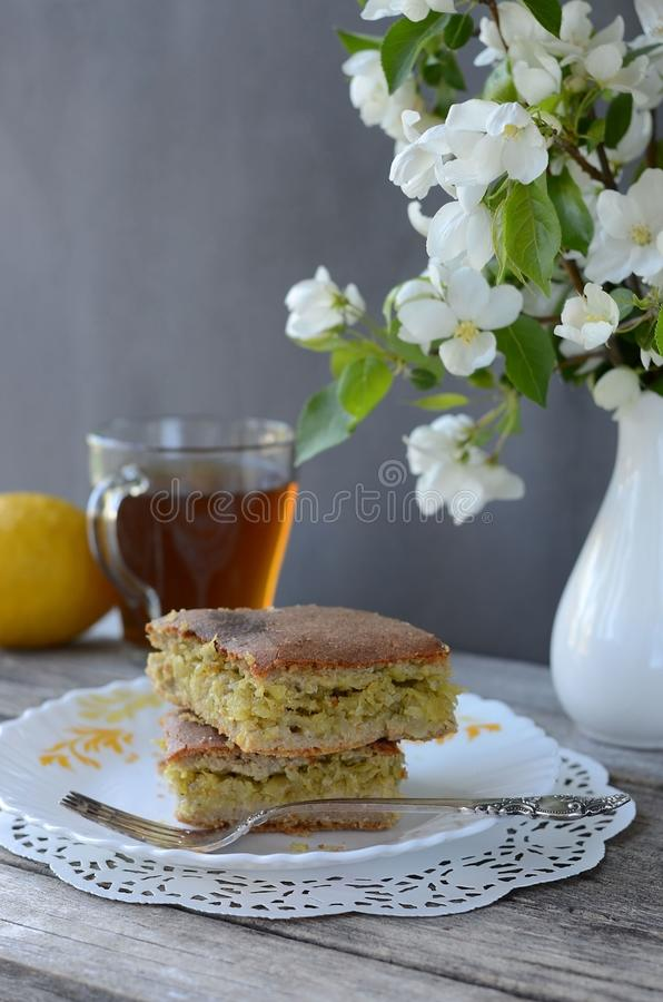 Pie with cabbage filling on a plate  with a vase of flowers. Bakery products royalty free stock photo