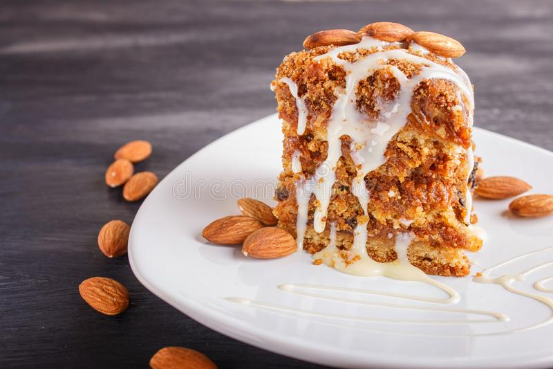 Pie with caramel, white milk sauce and almonds on a white plate on a black wooden background. Close up royalty free stock photography