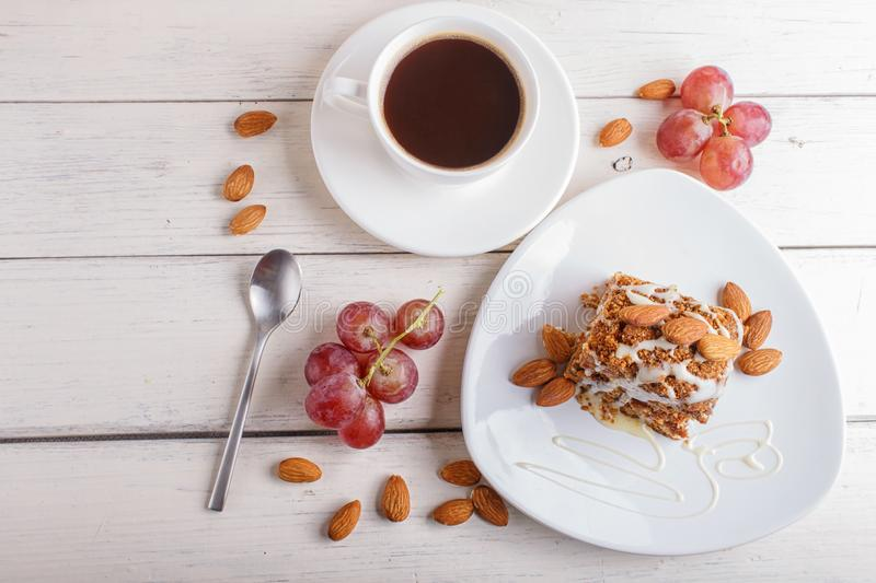 Pie with caramel, white milk sauce and almonds on a white plate on a white wooden background. Cup of coffee, top view, copy space stock image