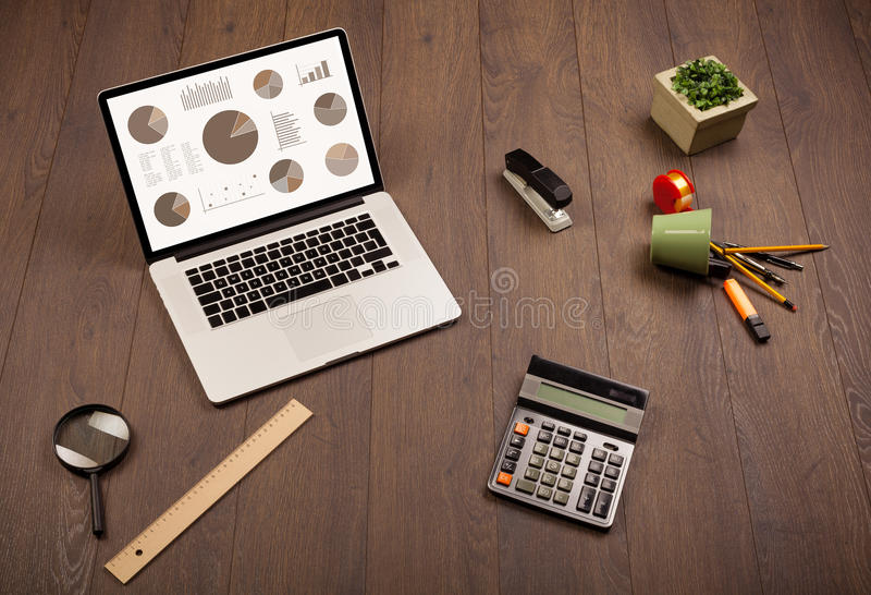 Pie chart graph icons on laptop screen with office accessories royalty free stock images