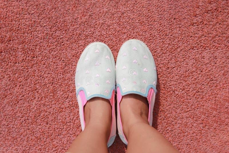 Pie de la mujer con las zapatillas de deporte en el estadio imagen de archivo