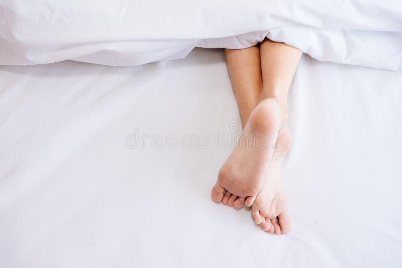 Pie de la mujer en la cama imagenes de archivo