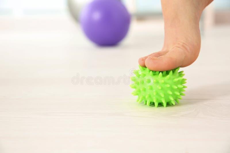 Pie de la mujer que hace ejercicios con la bola de la tensión fotos de archivo libres de regalías